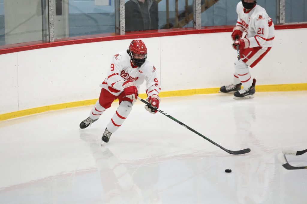 Junior Sean Garrity takes the puck out his zone .