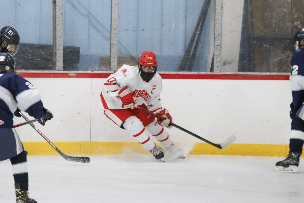 Even in the last minutes of the game, senior captain Tommy McNally fights for the puck.