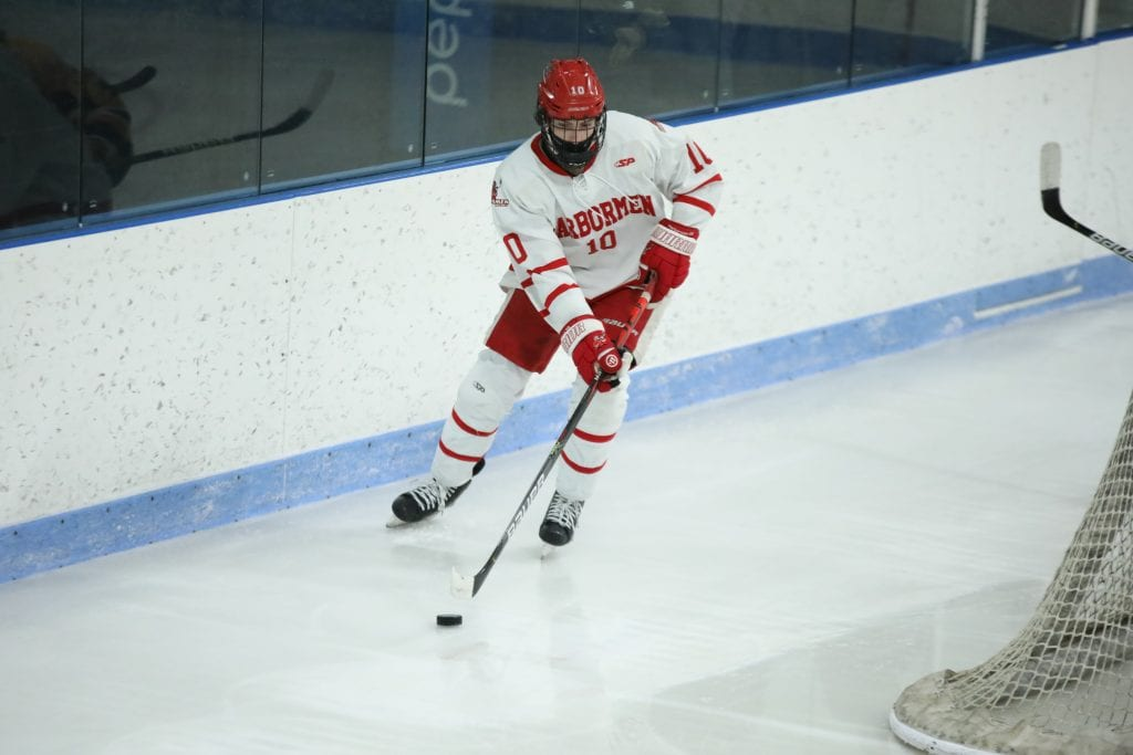 Junior Drew Carleton moves the puck behind his net.