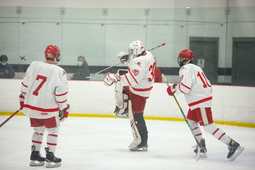 Senior goaltender Theo Jacobs celebrates Hingham's win after the final buzzer.
