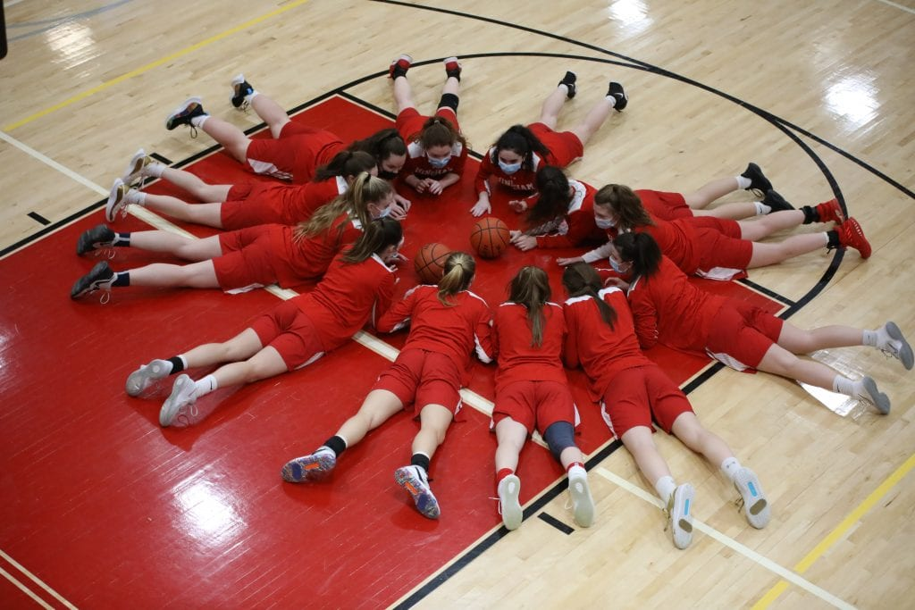 The team circles together on the floor before every game.