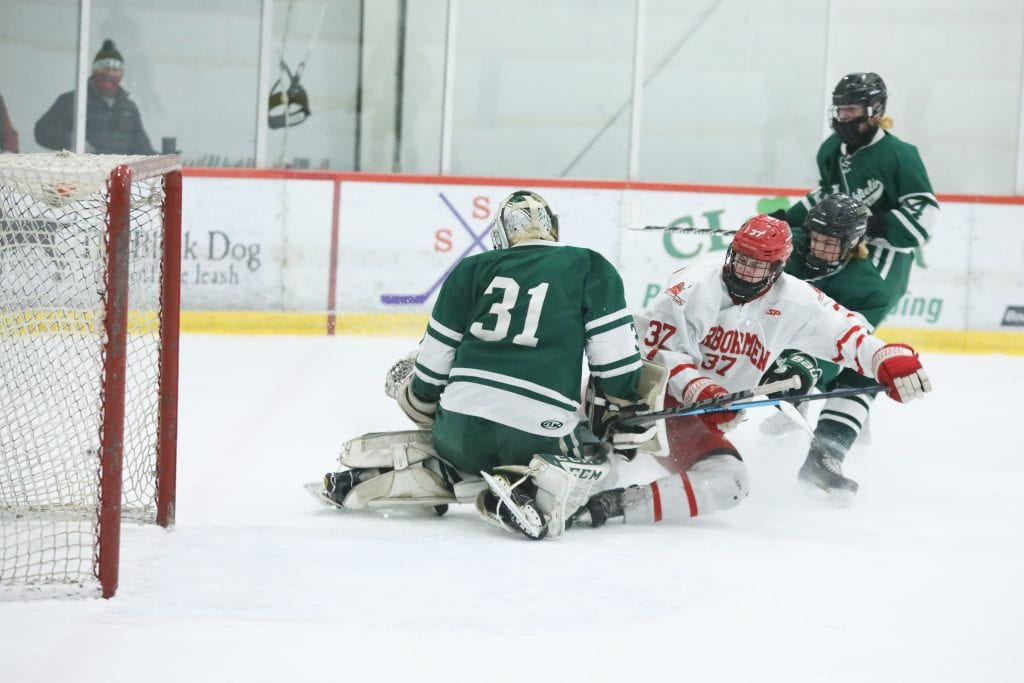 Sophomore Aidan Brazel gets pushed into the goalie in the first period.