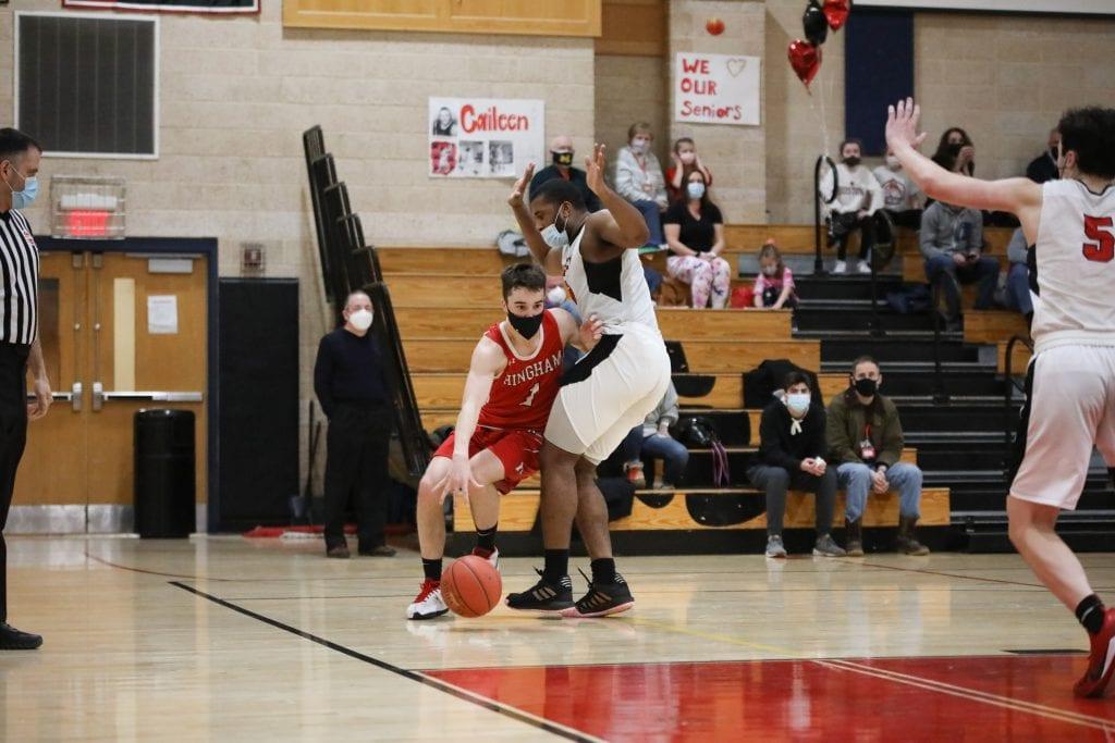 Senior Jack McBride tries to get around Whitman-Hanson's big man along the baseline.