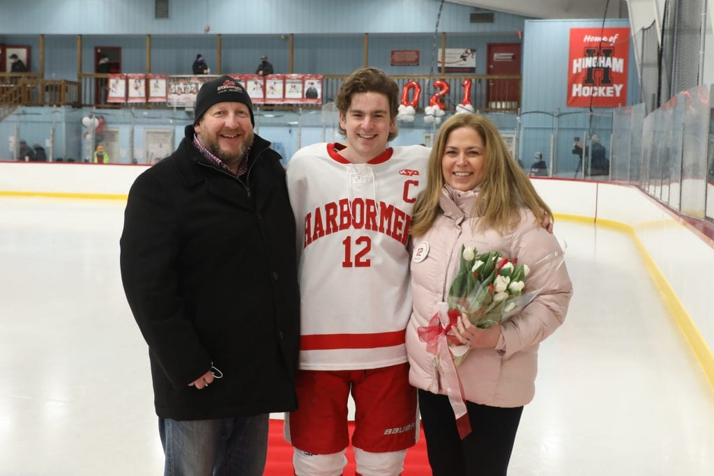 Captain Tommy McNally with his parents Jen and Kevin on senior night.