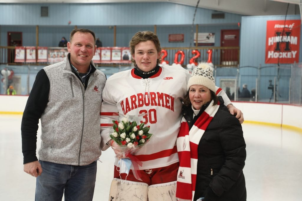 Theo Jacobs with his parents Terio and Jake on senior night.