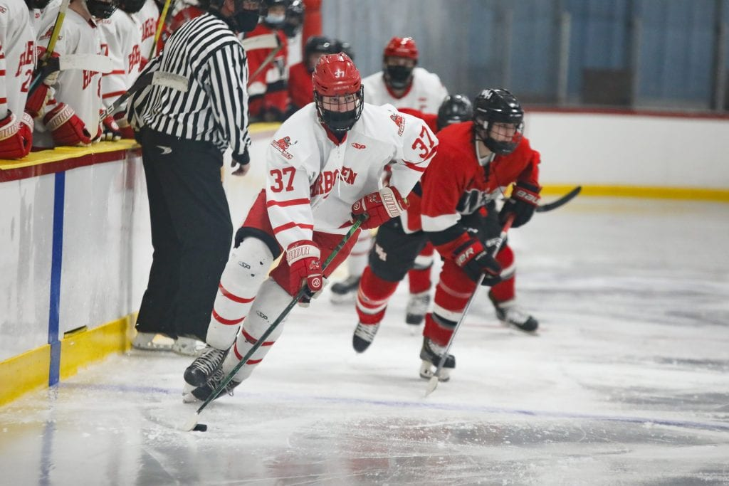 Sophomore Aidan Brazel takes the puck down ice along the boards.