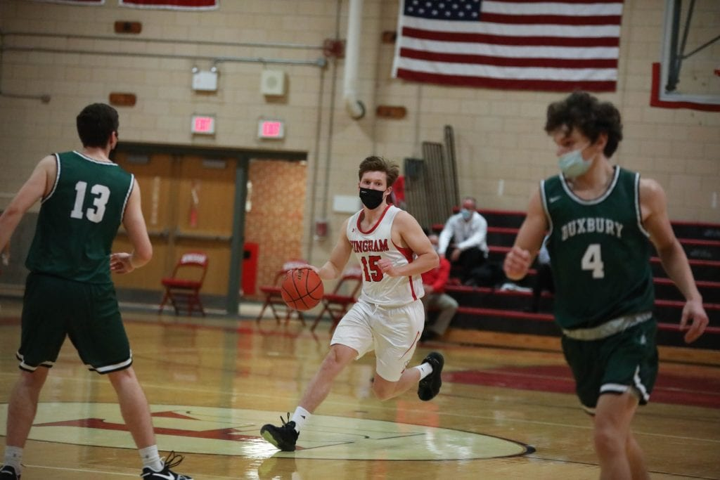 Senior Evan Williams brings the ball up the court in the first quarter.
