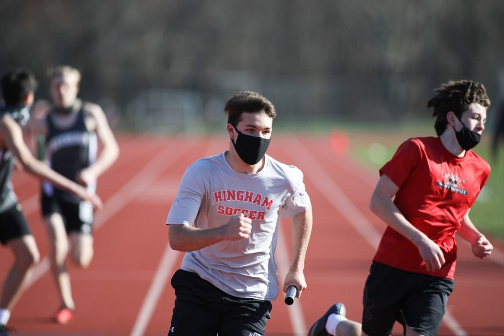 Sophomore Sam Benham takes the baton from sophomore Griffin Coppola in the 2x400.