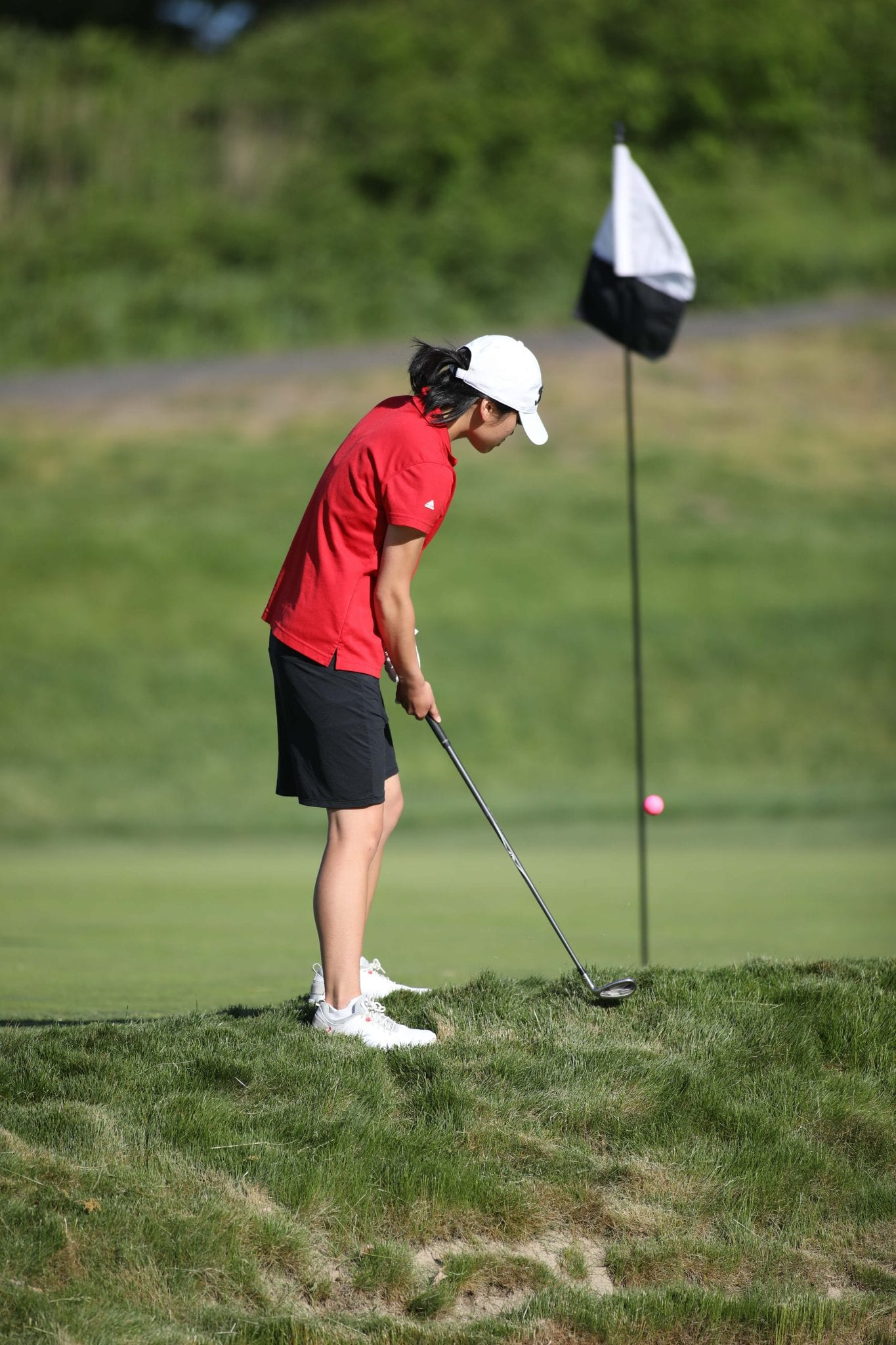 Junior Julie McAllister chips from just off the green on the third hole.