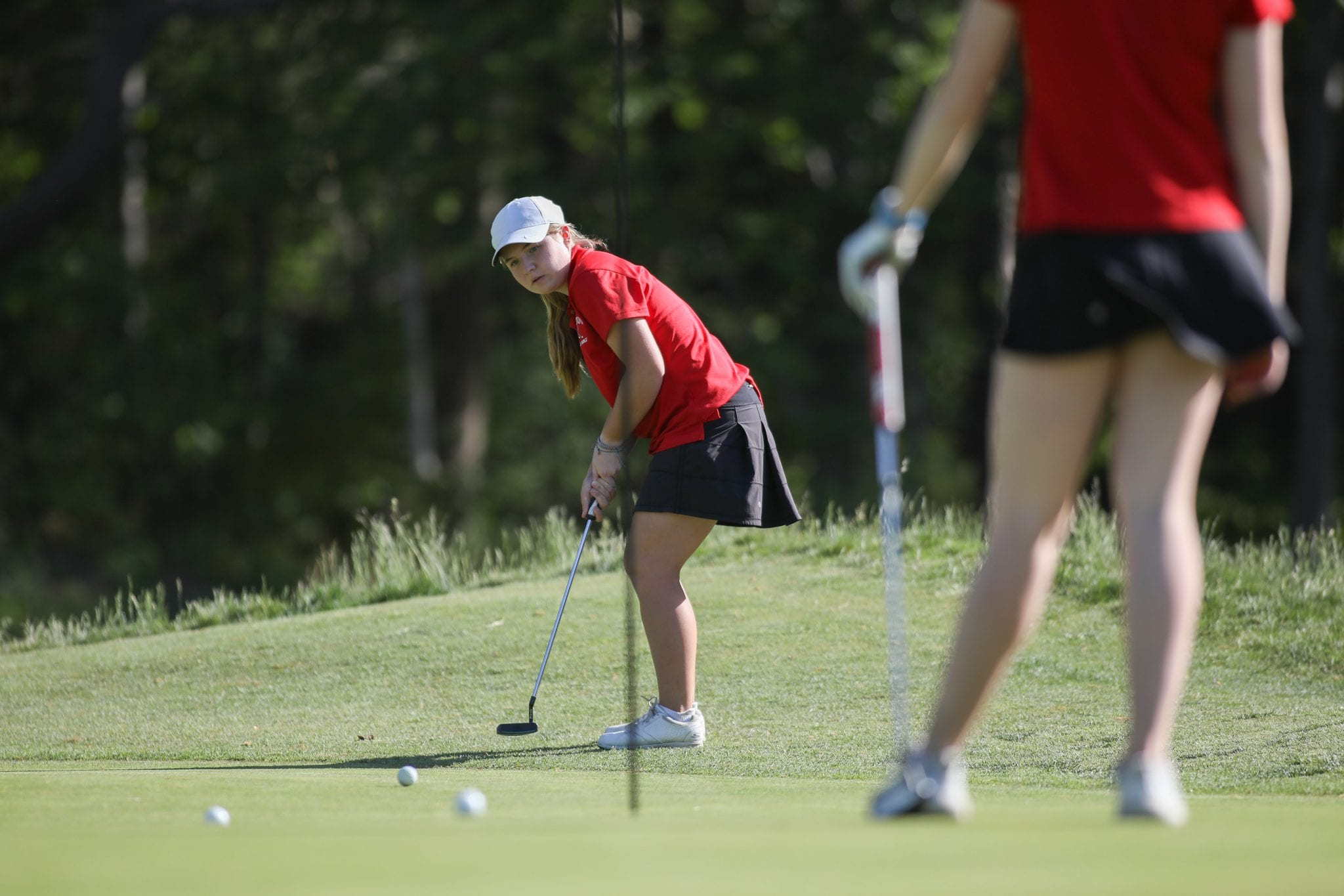 Sophomore Piper Jordan putts on the first hole.