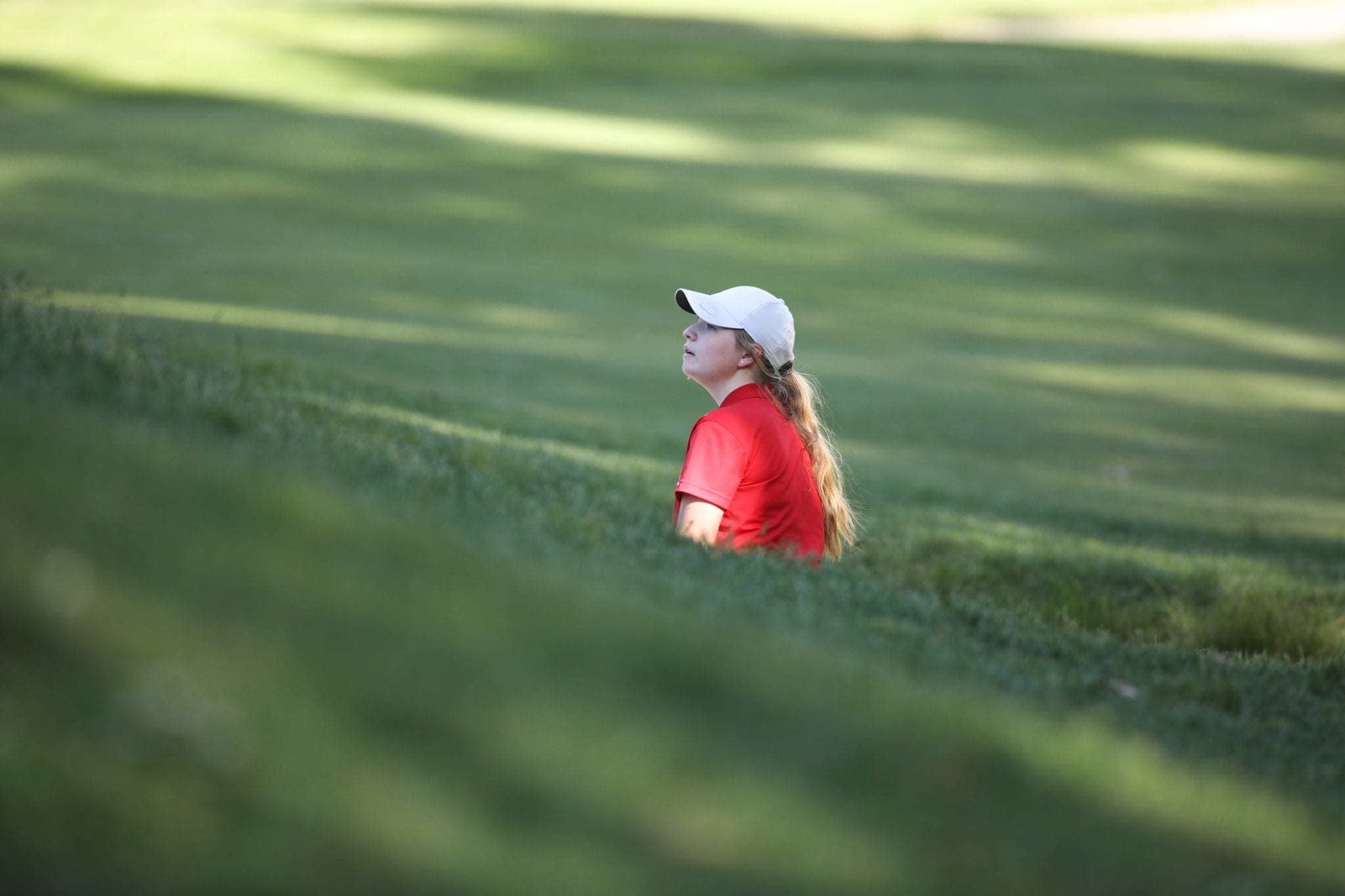 Sophomore Piper Jordan checks out where the pin is from the bunker well below the hole.