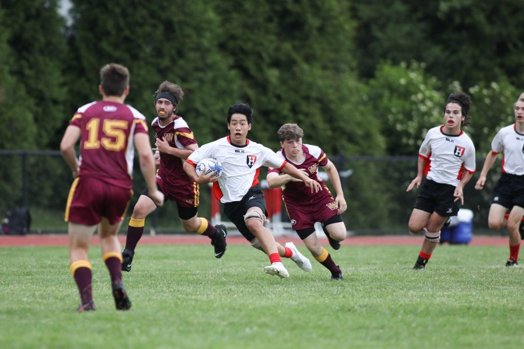 Sophomore Aiden Chan eludes tackles as he makes his way up field.