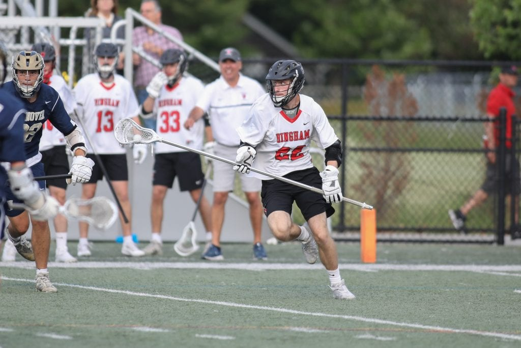 Senior Cooper Estes carries the ball late in the game as Hingham secures the win.