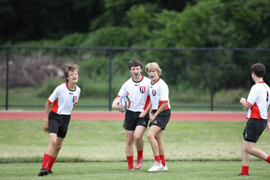 Sophomore Connor Rooney and senior John Thompson celebrate Jayce Mellish's try.
