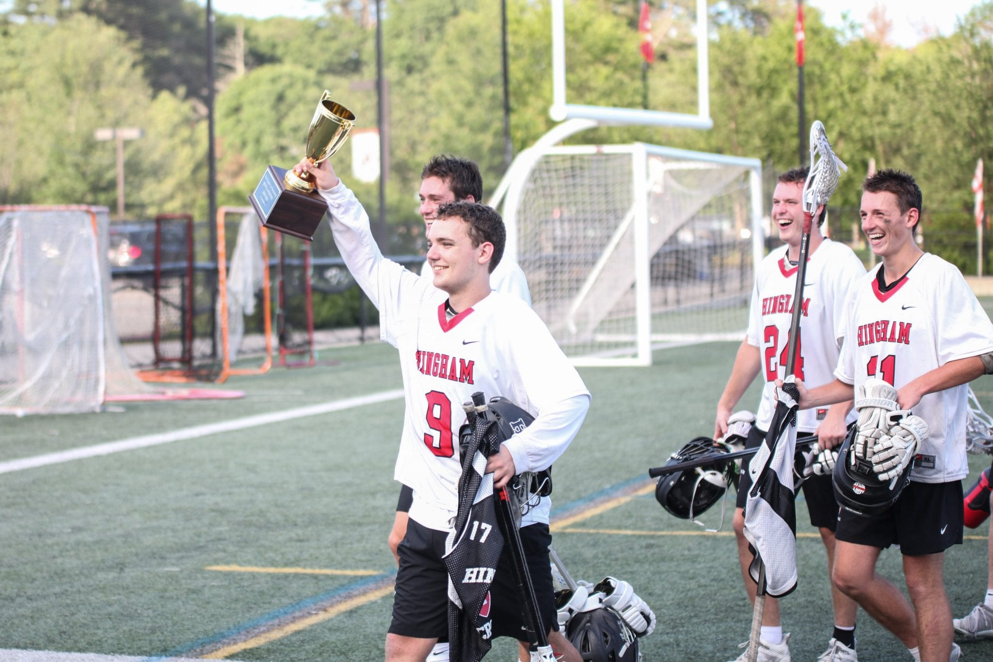 Senior captain and goalie Sam Bellomy leads his team off the field raising the Patriot Cup trophy high in air.