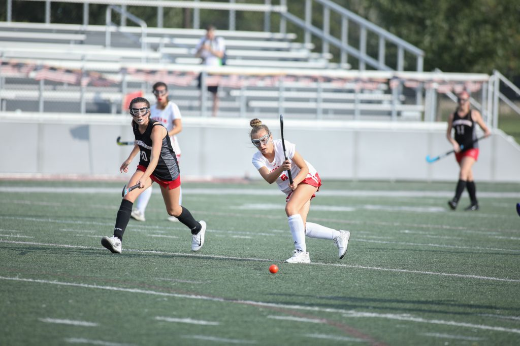 Junior Lily Ehler passes the ball to her teammate on the sideline.